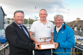 Friday 18th August 2017, Kinsale, Co. Cork Phil Plumtree, skipper of Swuzzlebubble receives the overall trophy from Thomas Roche, Commodore of Kinsale YC and Philippe Pilate, President of the Half Ton Class at the prize-giving for the Euro Car Parks Half Ton Classics Cup 2017 at Kinsale Yacht Club, Ireland. Photograph: David Branigan/Oceansport